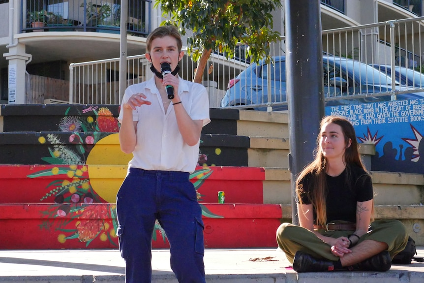 A young woman speaks into a microphone while another woman looks on.