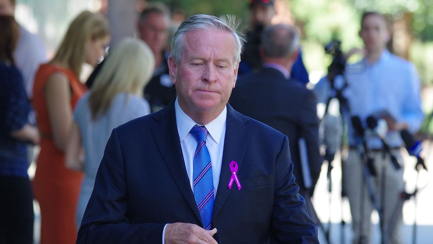 Colin Barnett looks downcast as he walks away from journalists, wearing a pink ribbon on his jacket.