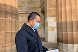 A man in a face mask standing outside of court