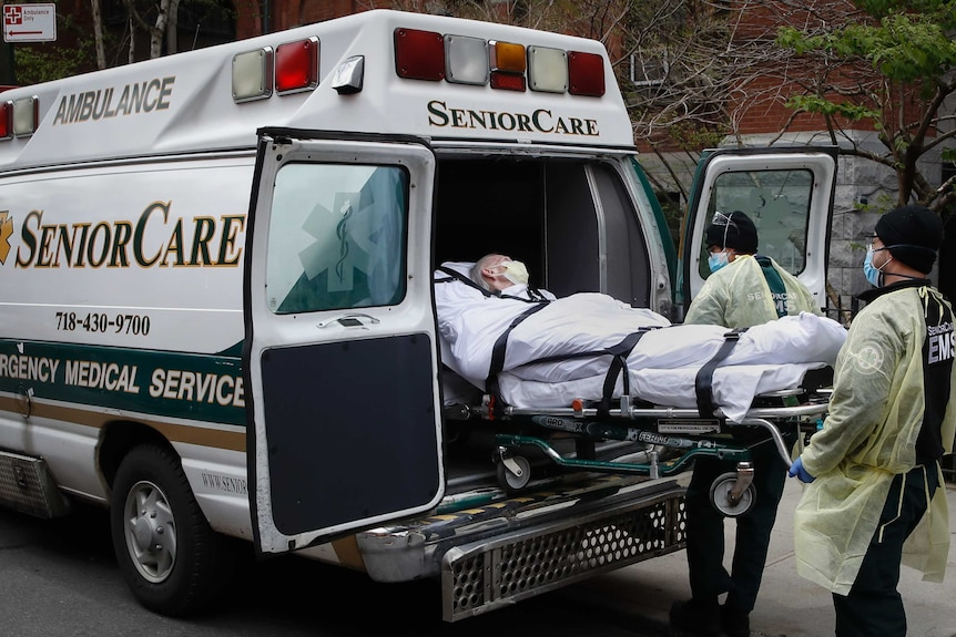 An older person with grey hair is loaded into an ambulance in a stretcher by medical workers wearing masks.