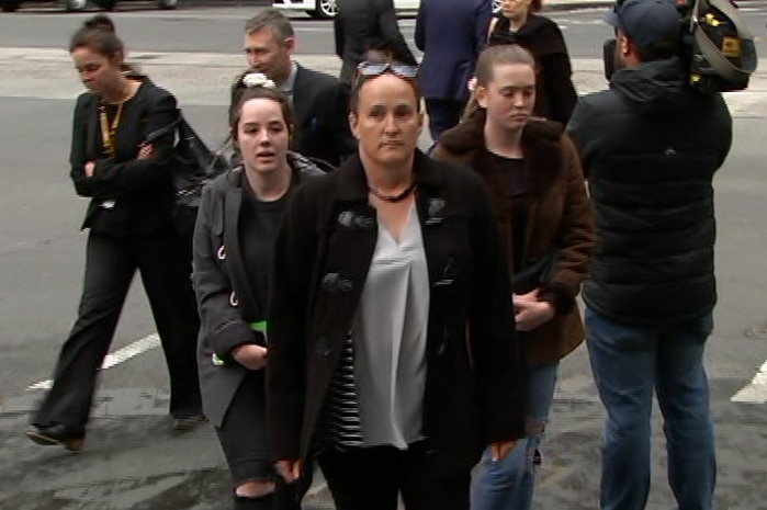 A woman walking in the street with other women next to her.