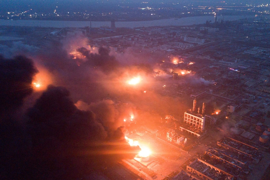 Overhead shot of fire blazing and smoke billowing in front of a night sky at the pesticide plant.