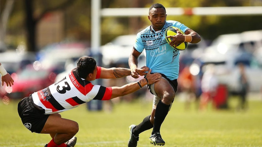 A Fijian Drua player running with the ball as a Canberra Vikings players attempts a tackle.