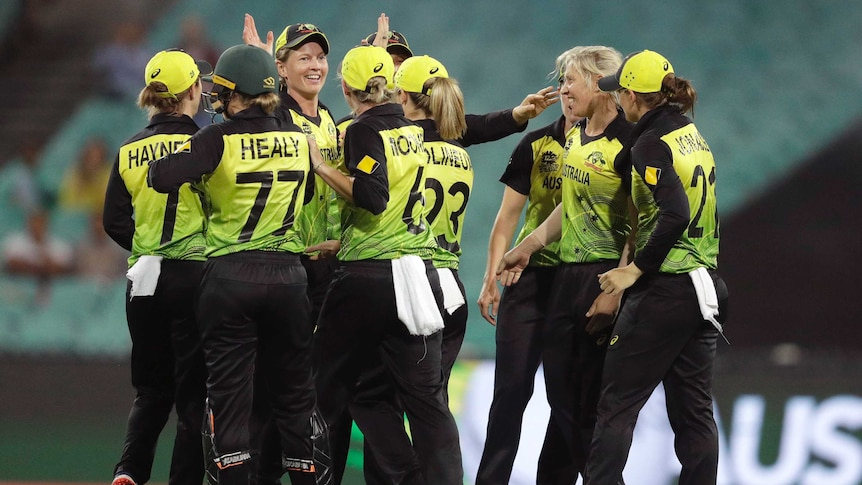 Australian women's cricketers high five after a wicket in the T20 World Cup semi-final.