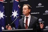 Federal Health Minister Greg Hunt gestures from a podium during a press conference.