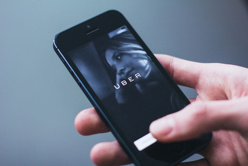 A woman uses the Uber app on her mobile phone.