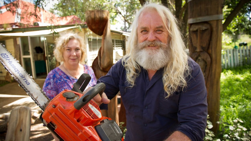 A long haired grey-bearded smiling man holds a chainsaw near a totem, while his wife, also an artist, looks on.