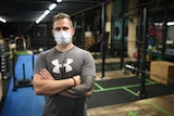 A man with tattoos and a face mask stands in an empty gym