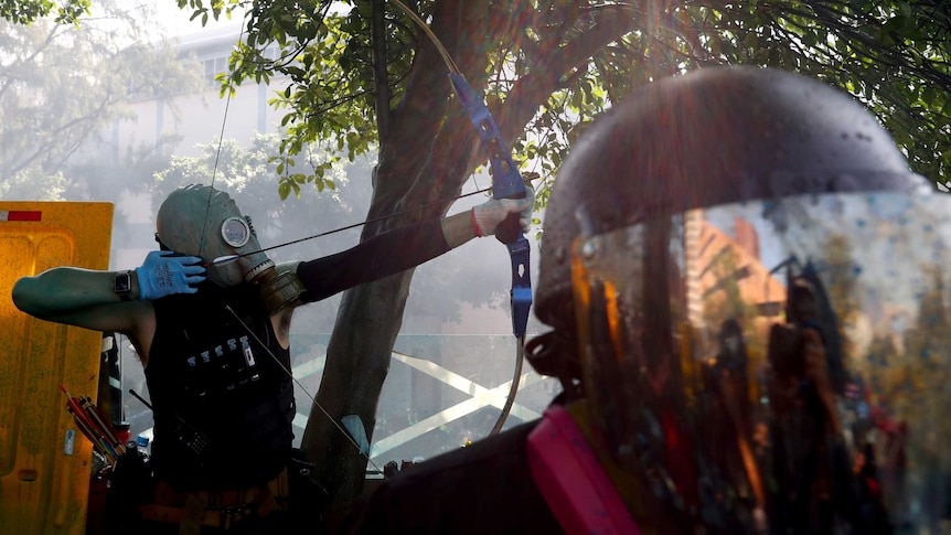 A protester wearing a black undershirt and oxygen mask shoots arrows in Hong Kong.