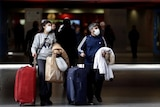 Passengers wearing face masks and rolling their suitcases through a railway station.