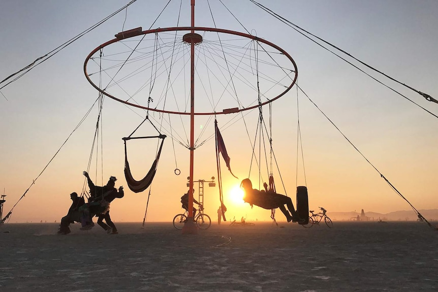 Revellers on a structure built with hammocks and swings in silhouette with the sun.