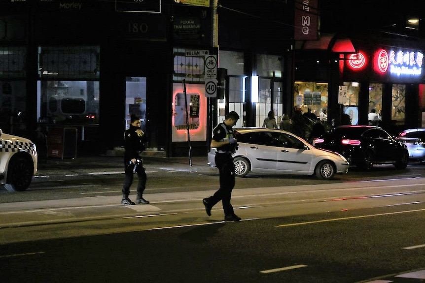 A male and a female police officer walk across a city road at night.