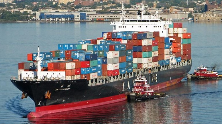 A large container ship close to the coast carrying a large load of shipping containers