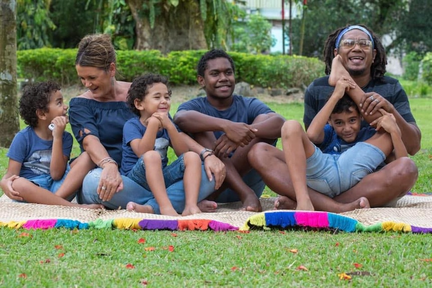 Family sit on mat outdoors, mother father and three sons dressed in jeans and grey t-shirts.