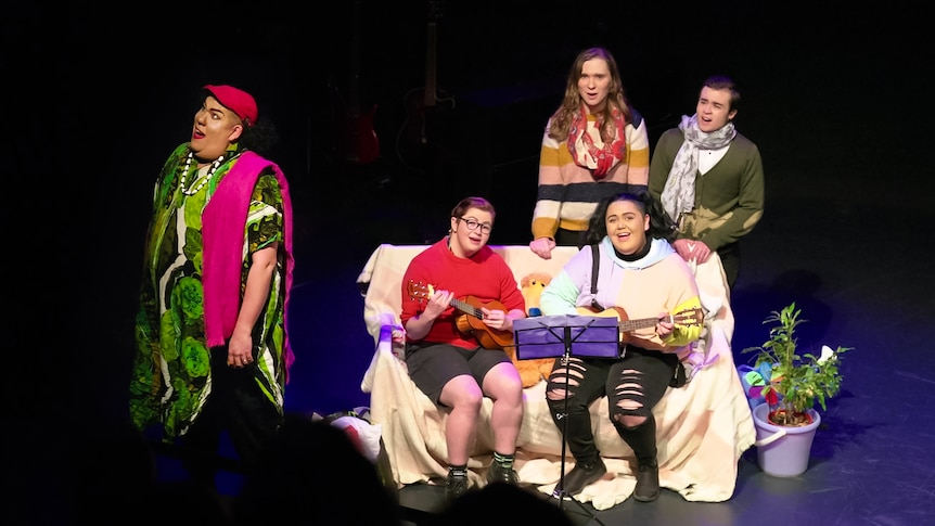 Five actors are performing a song on stage with ukuleles