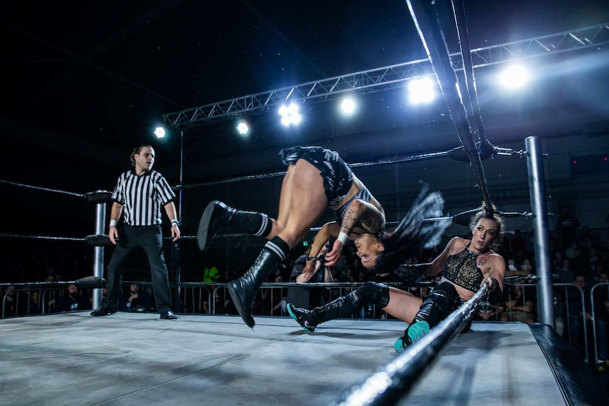 Two female wrestlers in a ring with referee in black-and-white uniform in left corner.