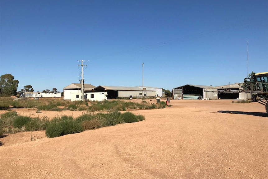 Aluminium sheds and farm equipment on a rural property.