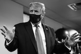 A black and white photo of US President Donald Trump wearing a facemask during a visit to a hospital.