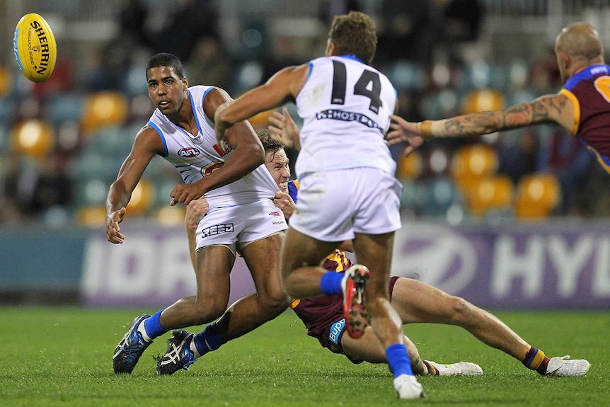 Joel Wilkinson, left, punches a yellow AFL ball in the direction of a teammate while being tackled