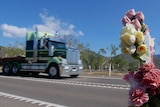 Fake flowers wrapped around a post by the Bruce Highway, a truck passes in the background.