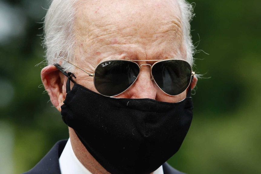 Grey-haired man with black sunglasses and facemask wearing a black suit and dark striped tie