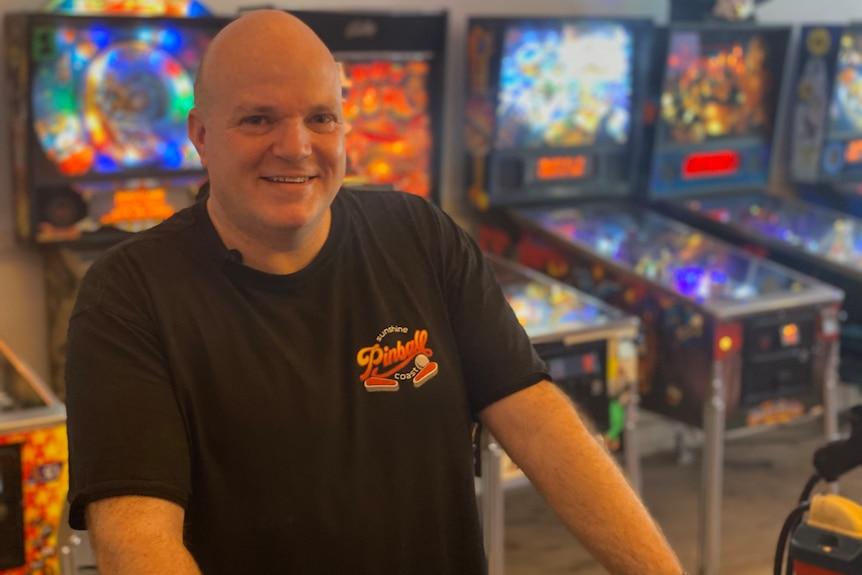 man standing in front of pinball machine