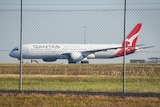 A Qantas plane on a tarmac behind a wired fence.