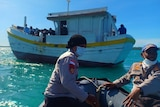 Indonesian police wear face masks as they head towards a wood boat.