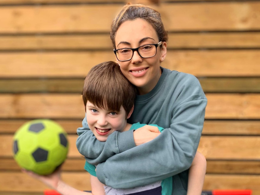 Sarah Goulding embraces her son, who is holding a soccer ball.
