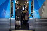 A woman stands in a Metro train as the doors close.