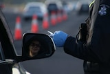 A driver's face in the side mirror as a gloved police officer's hand checks a driver's licence.