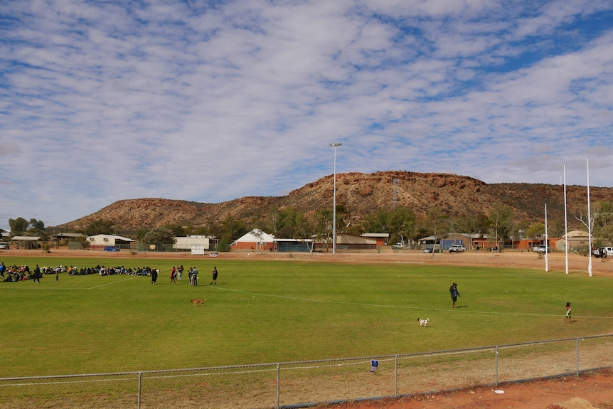 People on a green footy oval in Santa Teresa, with houses and a mountain range in the backdrop.