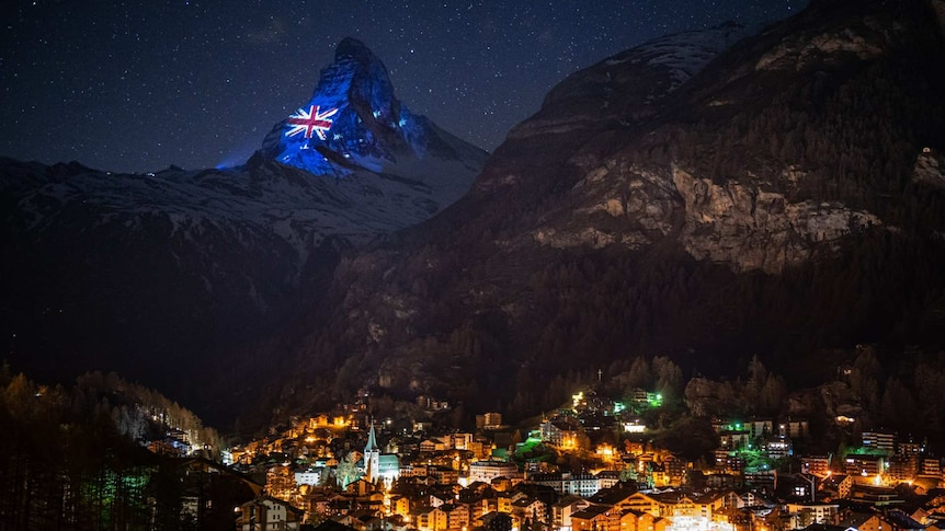 an australian flag image is projected on to the matterhorn mountain at night with houses illuminated below