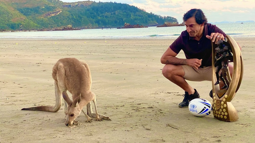 A man squats on a beach with a giant trophy while looking at a wallaby