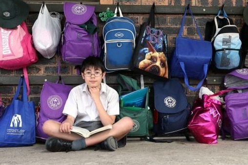 A teenage boy sitting on the ground in front of a school bag rack.