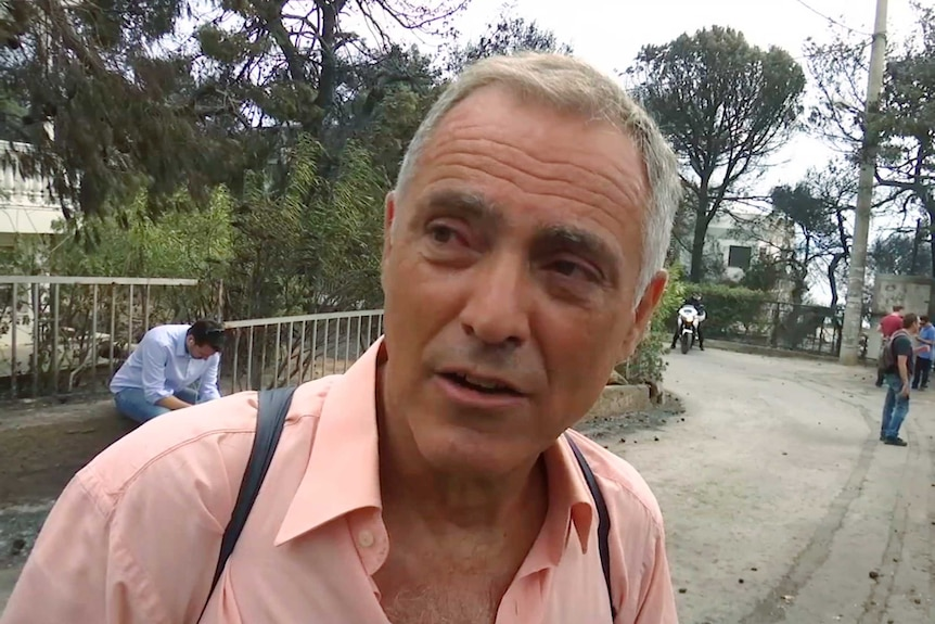 Nikos Stavrinidis, wearing a pink shirt, looks to the left of the screen.