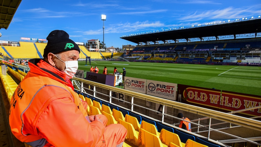 A steward sits in a football stadium with an orange coat on and a face mask