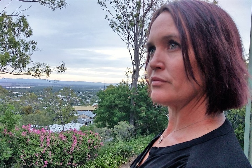 a woman with dark hair stands on her balcony looking off into the distance