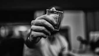 A man holds an American dollar note in front of his face.