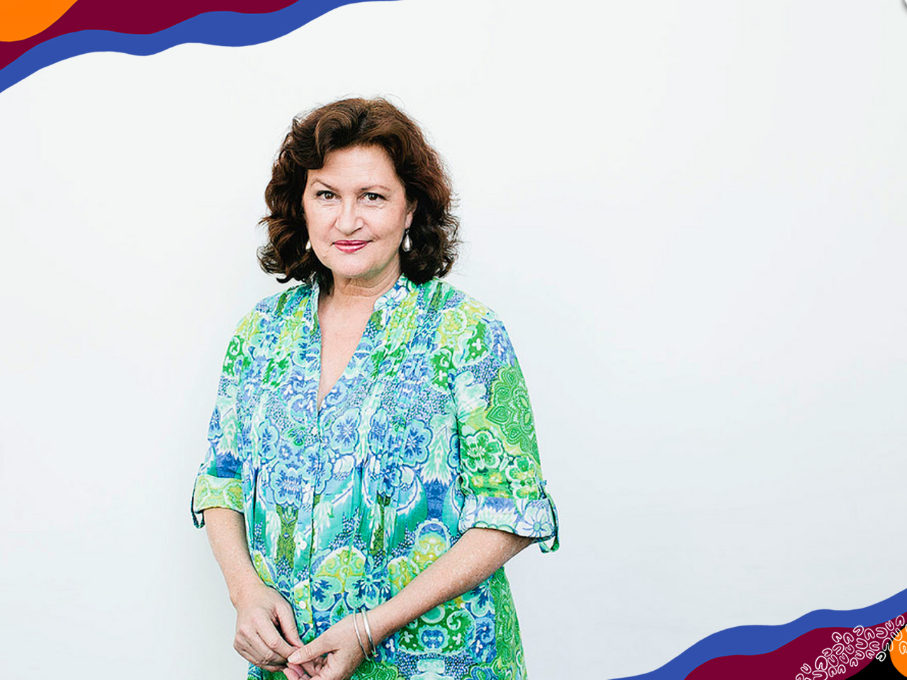 A woman with brown curly bob in lime green and blue patterned shirt stands in front of white wall.