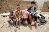 Boys sit on belongings at the rubble of houses destroyed by an air strike in the Okash village near Sanaa April 4, 2015