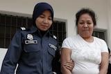 Maria Elvira Pinto Exposto escorted by a Malaysian customs officer outside court in Sepang, Kuala Lumpur
