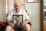 An elderly man sits in a chair holding a framed photo of his younger self on his knees.