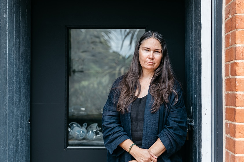 A woman with long dark hair and serious expression stands in wooden doorway of brick building.