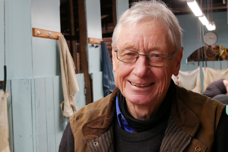 A man with white hair and glasses looks into the camera, he's wearing a brown leather vest