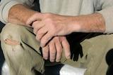 Male labourer's hands resting on knee
