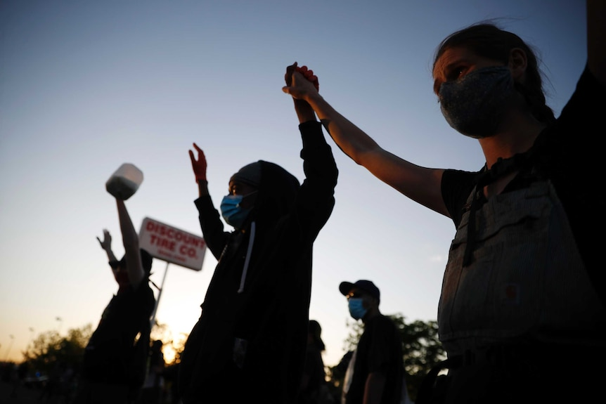 Three protesters are seen holding their hands up high, one holds a bottle with milk in it. The sky above indicates night's near.