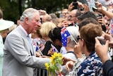 Prince Charles greets a crowd of people waving Australian flags and holding up mobile phones