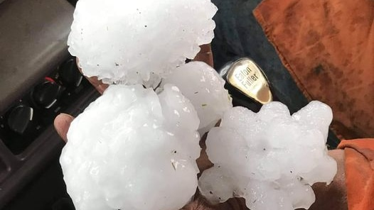 a man holds large white hailstones