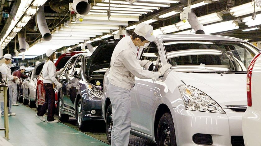 Workers install parts onto Toyota vehicles on the assembly line of the company's Tsutsumi factory in